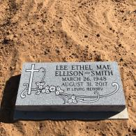 A flat headstone that is adorned with a cross and beautiful scroll featuring florals.