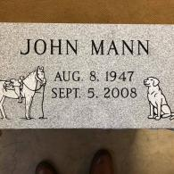 A flat headstone that features an etching of a horse & dog.