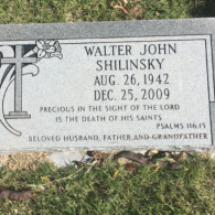 This flat headstone features a scripture as well as a cross.